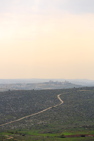 Road to a Palestinian village in a mountain near Hebron at sunset photo