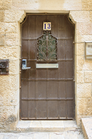 keylock: Brown door with number 13 on orange wall  in old city Jerusalem Editorial