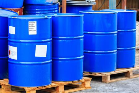 symbole chimique: Big Blue barils debout sur des palettes en bois sur une usine chimique Banque d'images