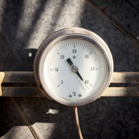 Round industrial thermometer isolated on gray metallic background photo