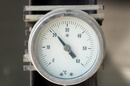 Industrial thermometer isolated on gray metallic background photo