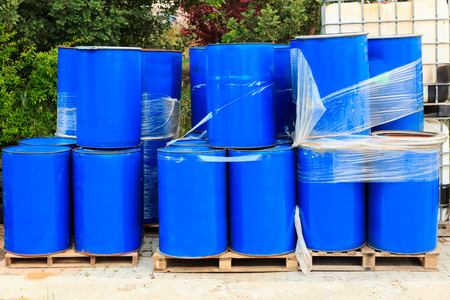 Old blue barrels standing on wooden pallets on a chemical plant photo