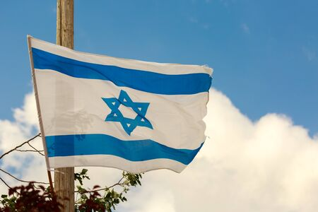 zionism: White and blue flag of Israel waving in the wind over the clouds in sky Stock Photo