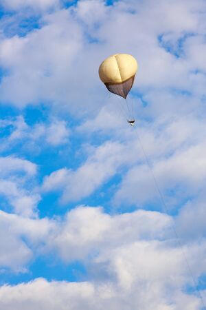 counterterrorism: Big white balloon over a white clouds in blue sky