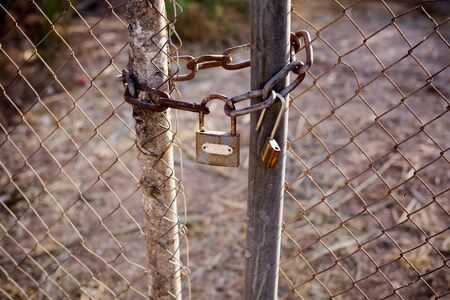 closed lock: Rusty lock and chain locking the gates of the mesh netting
