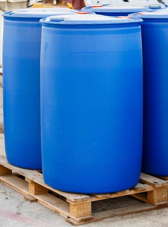 dangerous: Blue plastic barrels on pallet in a chemical plant