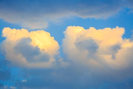 lite: Pair of lite golden sunset clouds on a blue sky