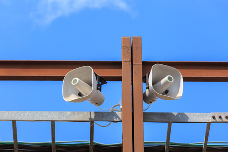 public address: Two big white loudspeakers on the brown metal construction