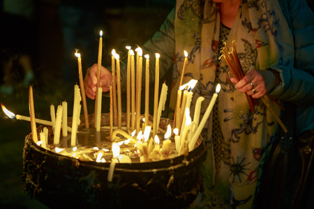 Religious Christian woman lights a candle in the Holy Sepulchre on Mount Calvary in Jerusalem
