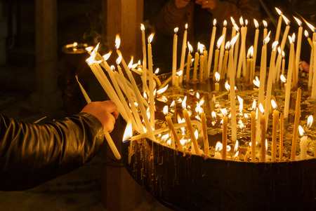 Pilgrim lights a candle in the Holy Sepulchre on Mount Calvary, Jerusalem, Israel
