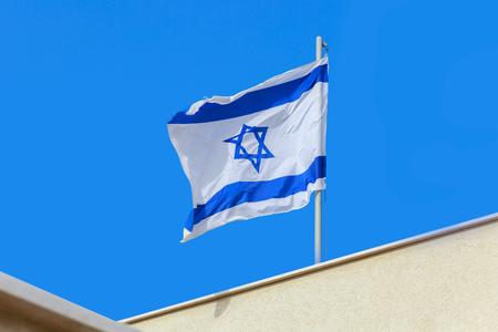 israeli: Flag of Israel waving on roof Stock Photo