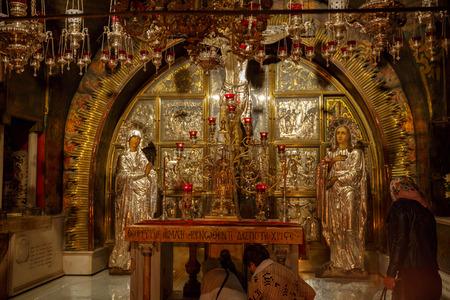 Jerusalem, Israel - Nov 06, 2016: pilgrims at Mount Calvary, on altar in Temple of the Holy Sepulchre, Jerusalem, Israel
