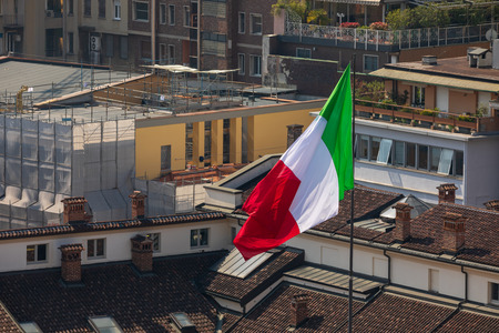 Large Italian red-white-green flag over the roofs Imagens