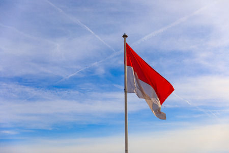 National flag of principality Monaco against blue sky background Imagens - 124884227