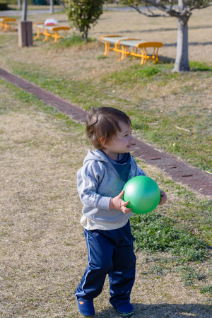 2 year old: A 2 year old boy holding a ball and smiling at a playground. Stock Photo