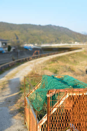 dirt path: A rusty container for garbage next to a dirt path following the curve of a river with mountains in the background. In the countryside of Kochi, Japan. Stock Photo