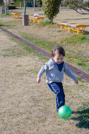 2 year old: A 2 year old boy kicking a ball in a park.