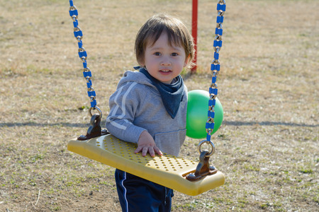 A 2 year old boy holding a ball and standing by the swings at a playground.