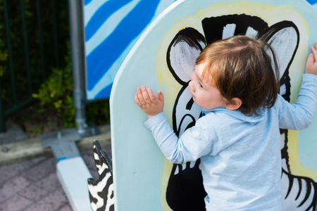 olds: A 2 year old boy hugging a painting of a zebra at a zoo.