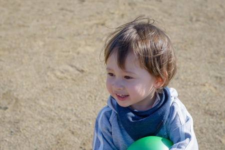 2 year old: A 2 year old boy holding a green ball smiling in a playground.