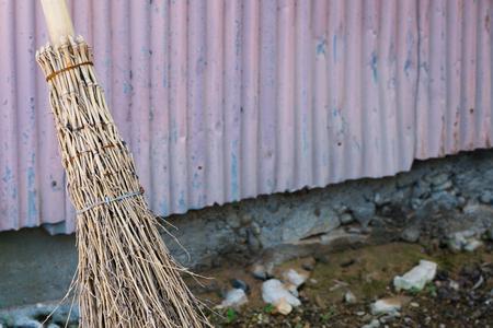 古い外壁にもたれてわら竹ほうき。