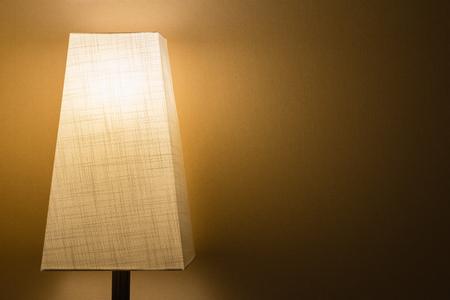 シンプルな壁に暗い部屋で布のランプ シェードとランプ。