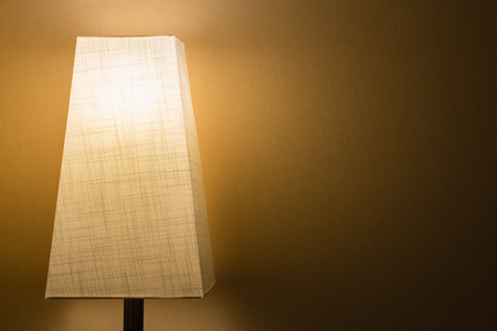 A lamp with a cloth lamp shade in a dark room against a simple wall.