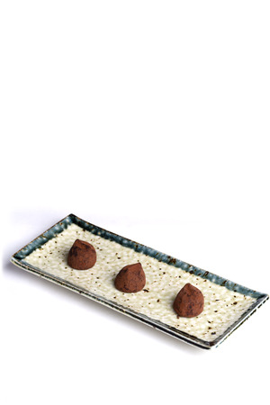 chocolate truffles: Three chocolate truffles on a ceramic plate with a pure white background.