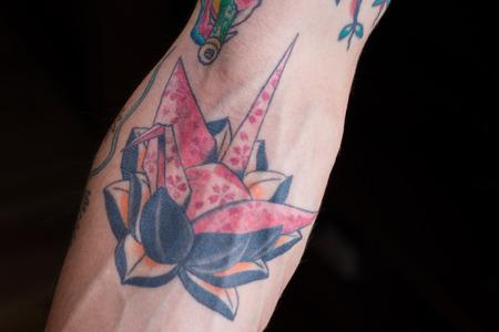 검은 색과 오렌지색 로터스에 벚꽃 꽃잎 디자인 핑크 종이 접기 크레인의 문신.