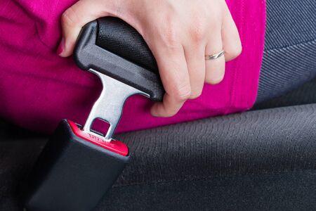 cinturon de seguridad: Una chica que llevaba una camisa de color rosa pandeo un cinturón de seguridad Foto de archivo