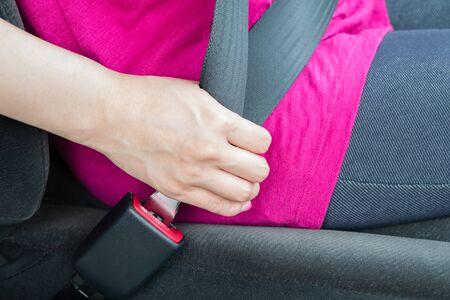 seatbelt: A girl wearing a pink shirt buckling a seatbelt Stock Photo