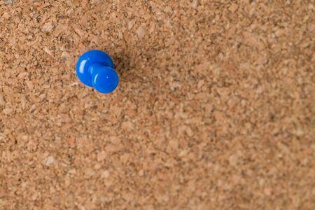 tack board: A single blue thumb tack on a cork board. Stock Photo