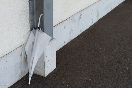 A dirty old forgotten umbrella at a train station.