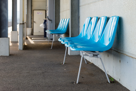vacancies: Empty plastic blue chairs at a train station in the countryside of Kochi, Japan.