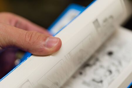paperback: A close up of a hand flipping through the pages of a paperback book.