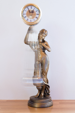 pendulum: A classic looking bronze statue clock with a swinging pendulum. Stock Photo