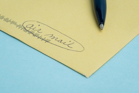 """comunicación escrita: Un envenlope amarilla con las palabras """"correo aéreo"""", escrita a mano en pluma con la pluma situada en la parte superior y un fondo azul. Foto de archivo"""