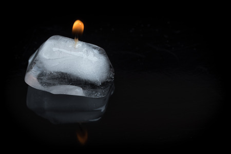 contradict: A close up shot of a lit candle wick stuck into an ice cube on a black background with reflection.