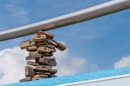 meant: Molti serrature bloccate intorno ad un palo rapporti simboleggiano destinate a durare. Un cielo blu con nuvole in background.