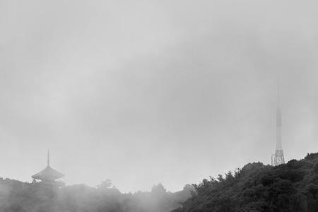 radio tower: A black and white photo of an old Japanese Pagoda next to a modern radio tower on top of a mountain on a rainy, foggy day.
