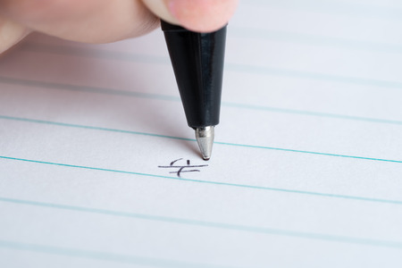 kanji: A macro shot of a hand writing the Japanese Kanji for happy or happiness on white lined paper. Stock Photo