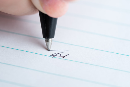 kanji: A macro shot of a hand writing the Japanese Kanji for smile or laugh on white lined paper. Stock Photo