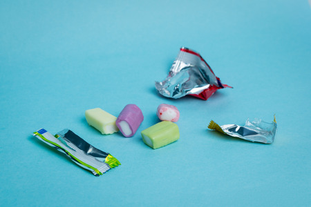 chewy: Strawberry, grape, banana and green apple chewy candies and their open wrappers on a blue background. Stock Photo