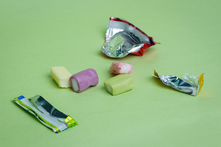 chewy: Strawberry, grape, banana and green apple chewy candies and their open wrappers on a green background.