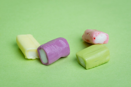 chewy: Strawberry, grape, banana and green apple chewy candies on a green background.