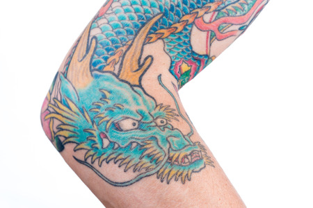 A detailed shot of a blue/green dragon tattoo in Japanese style on the forearm, elbow and bicep of a white male isolated on a white background. 版權商用圖片