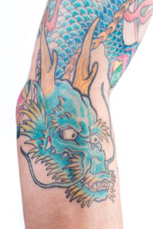 tatouage dragon: Un tir d�taill�e d'un  vert tatouage de dragon bleu dans le style japonais sur l'avant-bras, le coude et biceps d'un homme de race blanche isol� sur un fond blanc. Banque d'images