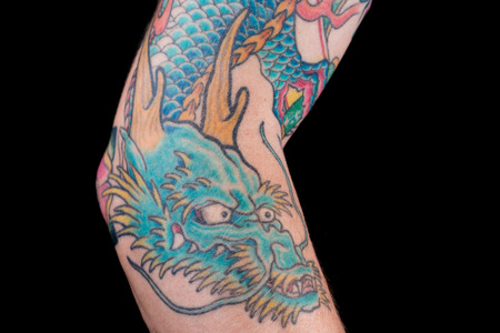 arm tattoo: A detailed shot of a bluegreen dragon tattoo in Japanese style on the forearm, elbow and bicep of a white male isolated on a black background.