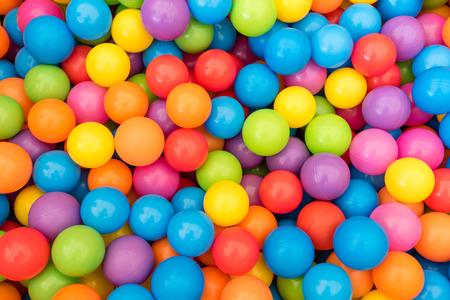 pelota: Muchas pelotas de plástico de colores en Ballpit para niños en un patio.