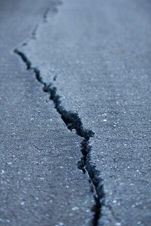paved: A long windy crack on a paved street. Stock Photo